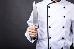 Closeup of a chef  holding a big sharp knife. Over gray background Stock Image