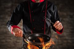 Closeup of chef holding frying pan above grill. Closeup of chef holding empty frying pan above grill. Concept of food preparation, ready for product placement royalty free stock photo
