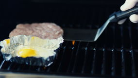 Closeup of chef preparing egg and cutlet for black burger on grilln at restaurant kitchen. Closeup of chef preparing egg and cutlet for black burger on grill at stock footage