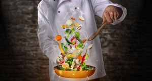 Closeup of chef preparing vegetable on pan. Closeup of chef cooker preparing vegetable on fire, flying motion effect. Old brick wall on background Royalty Free Stock Images