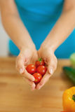 Closeup on cherry tomato in hand of housewife. In kitchen Royalty Free Stock Photo