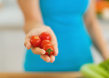 Closeup on cherry tomato in hand of woman. In kitchen Stock Photography