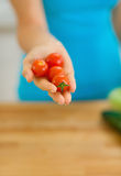 Closeup on cherry tomato in hand of young woman. In kitchen Royalty Free Stock Photo