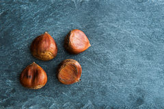 Closeup on chestnuts on stone substrate Royalty Free Stock Photo