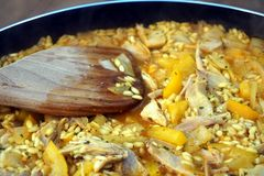 Closeup of chicken and pepper paella in a pan with wooden spoon.  Royalty Free Stock Photos