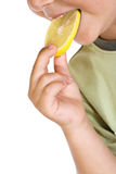 Closeup of child eating lemon slice Royalty Free Stock Photography