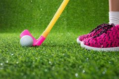 Closeup of a child golfer with putter and ball. Putting on green grass Stock Image