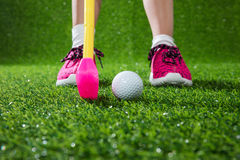Closeup of a child golfer with putter and ball. Putting on green grass Royalty Free Stock Image