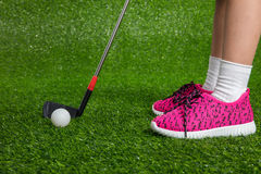 Closeup of a child golfer with putter and ball. Putting on green grass Stock Images