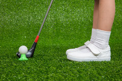 Closeup of a child golfer with putter and ball. Putting on green grass Stock Photography