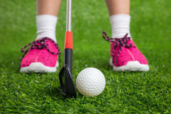 Closeup of a child golfer with putter and ball. Putting on green grass Royalty Free Stock Images