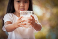 Closeup child hand holding a glass of milk Stock Photography
