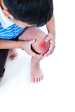 Closeup of child injured at knee. Isolated on white background. Child injured. Closeup of asian child injured at knee. Sad boy looking at bruise with a painful Royalty Free Stock Photos