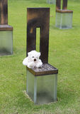 Closeup child`s empty chair with White Teddy Bear, Oklahoma City Memorial. Pictured is a small white teddy bear placed by a visitor on an empty child`s chair in stock images