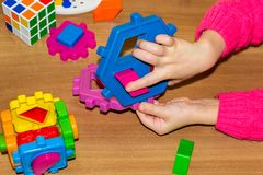 Closeup of child& x27;s hand taking bright mosaic parts, learning colors at home stock photo