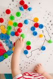 Closeup of child`s hand taking bright mosaic parts. Playing and learning colors at home. Toddler boy playing with colorful constr royalty free stock photos