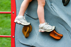 Closeup Child's Legs on Rock Wall Stock Images