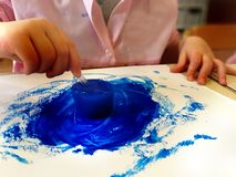 Closeup of children hands painting during a school activity - ice painting - learning by doing, education and art, art therapy. Concept stock photos