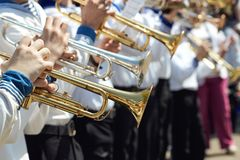 Closeup of a children`s orchestra playing on musical wind instru. Ments in the park Stock Photos