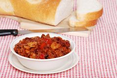 Closeup chili with spoon. With fresh bread in the background royalty free stock photos