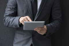 Closeup of a Chinese business mans hands holding a tablet computer. Stock Photography