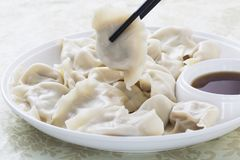 Closeup of Chinese food JIAOZI, Dumpling with chopsticks. Royalty Free Stock Photos