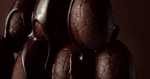 Closeup of chocolate eggs and falling liquid chocolate on it stock video footage