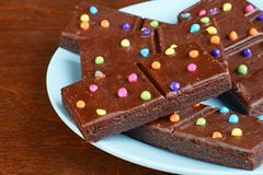 Closeup chocolate fudge brownies with candy pieces on blue plate stock photos