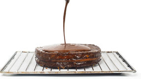 Closeup of chocolate icing pouring over Sacher torte Stock Image