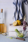 Closeup of chopped leek and lemons on kitchen table, bottle of white wine and towel in the background. Royalty Free Stock Images