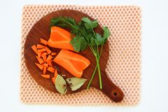 Closeup of chopping board with fresh carrot, greenery, laurel le Royalty Free Stock Image