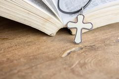 Closeup christian cross and bible on old wooden table with sunlight. christian concept Jesus is the light of the world. Copy space for design royalty free stock photography