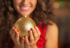 Closeup on christmas ball in hand of smiling woman in red dress Stock Image