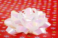 Closeup christmas bow on snowflake paper Stock Photo