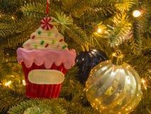 Closeup of Christmas cupcake with gold ball and bokeh lighting. stock photography