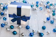Closeup Christmas gift with blue ribbon and silver and blue Christmas balls and garland on white wooden background.  royalty free stock image