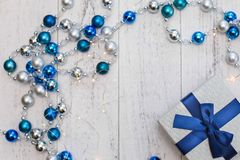 Closeup Christmas gift with blue ribbon and silver and blue Christmas balls and garland on white wooden background.  royalty free stock photos