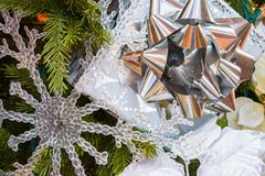 Closeup Christmas Ornaments on Decorated Tree. Close up of Gift Wrapped Christmas Present with Silver Bow and Snowflake Ornaments on Tree Filling Frame royalty free stock photography