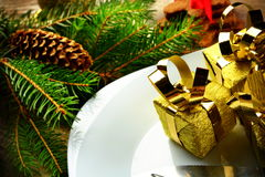 Closeup Christmas plate golden gifts pines wooden surface Royalty Free Stock Photos