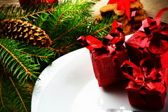 Closeup Christmas plate red gifts pines wooden surface Stock Photos