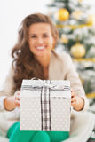 Closeup on christmas present box giving by happy young woman Stock Images