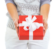 Closeup on christmas present box giving by young woman Royalty Free Stock Photos