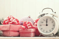 Closeup christmas present with a toy, white alarm clock Royalty Free Stock Image