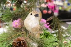 Closeup of Christmas straw bird perched on an artificial tree with pine cones with pink and colorful bokeh background stock image
