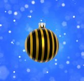 Bauble and falling snowflakes. Closeup of Christmas tree decoration with black and gold stripes and blurred background of blue sky and falling snowflakes stock image