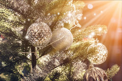 Closeup of Christmas-tree with decorations items. In light and bokeh background with light flare effect christmas and newyear festive concept Royalty Free Stock Images