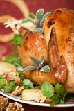 Closeup of Christmas turkey on dinner table. Christmas turkey served with herbs, baked potatoes and walnuts on holiday table Stock Images