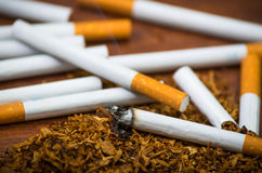Closeup cigarettes and tobacco lying around on wooden surface, anti smoking concept Stock Photography