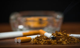 Closeup cigarettes and tobacco lying inside and around glass ash tray on wooden surface, anti smoking concept Stock Photography