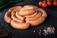 Closeup circle of raw short sausages on black background. Closeup circle of raw short thick meat sausages served with pink salt, spices, green onion and tomatoes royalty free stock image